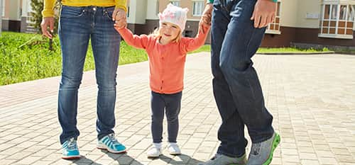 toddler holding hands with two adults
