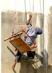 painter hanging precariously