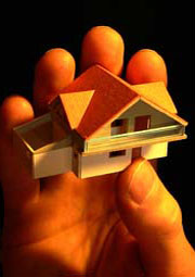 Hand holding miniature house