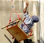 painter on teetering scaffolding