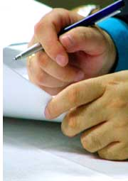 hands and pen signing a document